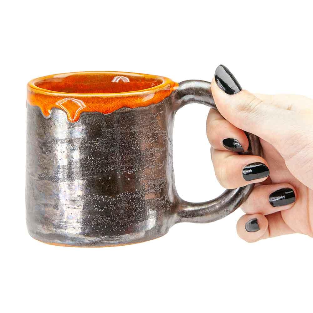 Fém hatású, mázas kerámia bögre füllel, női kézben. Narancssárga perem. Ipari dizájn. 2dl.