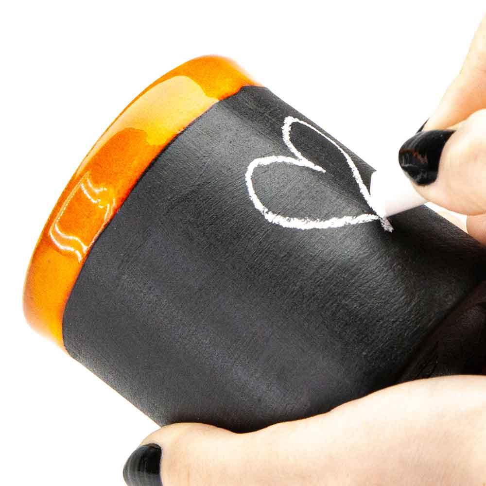 Táblakrétával írható-rajzolható bögre. Narancssárga szegély. 2dl. Női kéz krétával szívet rajzol a bögrére.