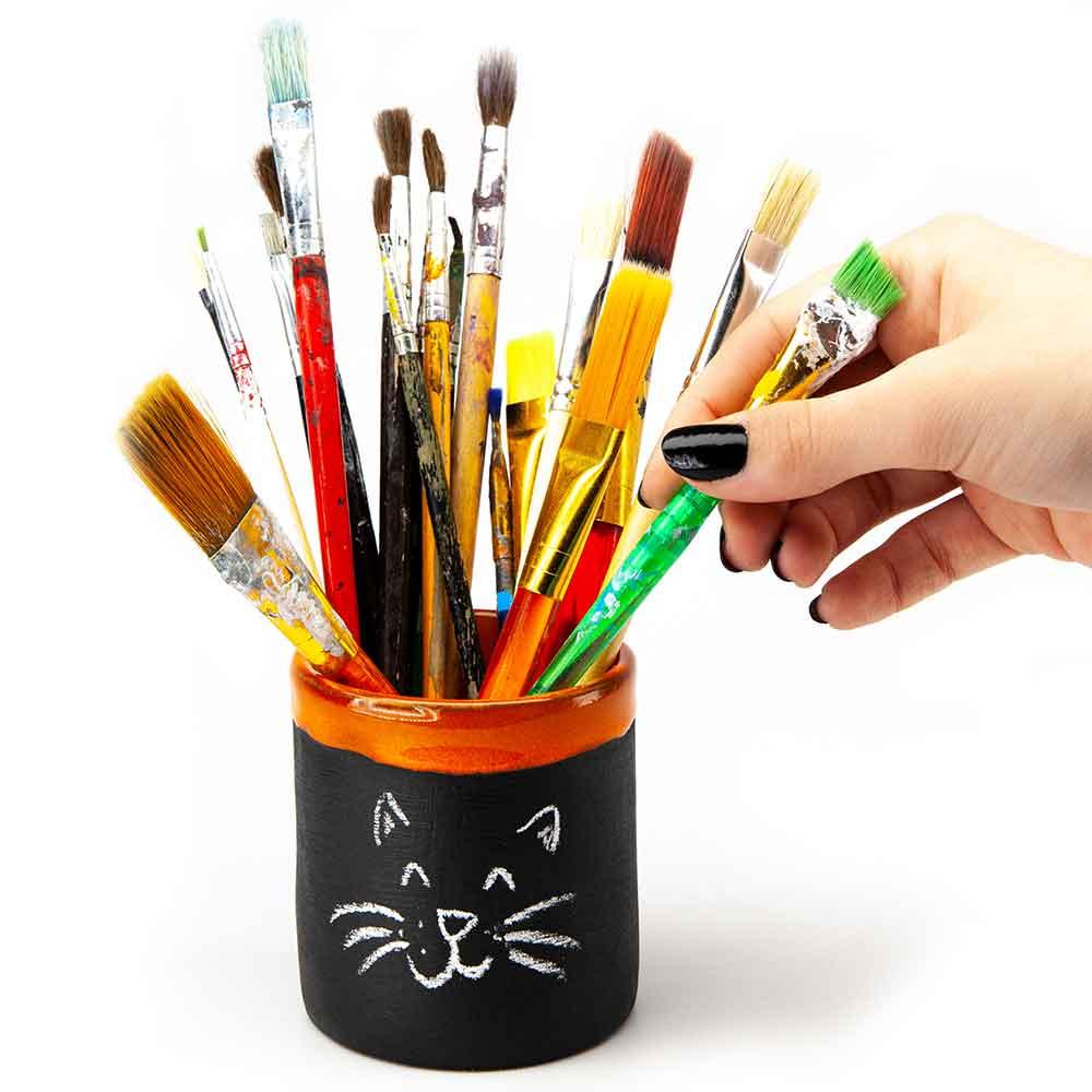 Táblakrétával írható-rajzolható bögre. Narancssárga szegély. 2dl. Ecsettartó bögre. Női kéz ecsetet rak a bögrébe.