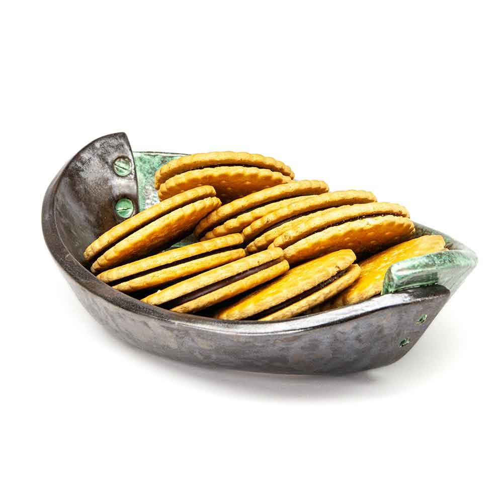 Átlapolt csavar díszítésű, fém hatású mázas ovális kerámia tál csokiskekszszel. Zöld-szürke fémes máz. Ipari dizájn. Loft design.